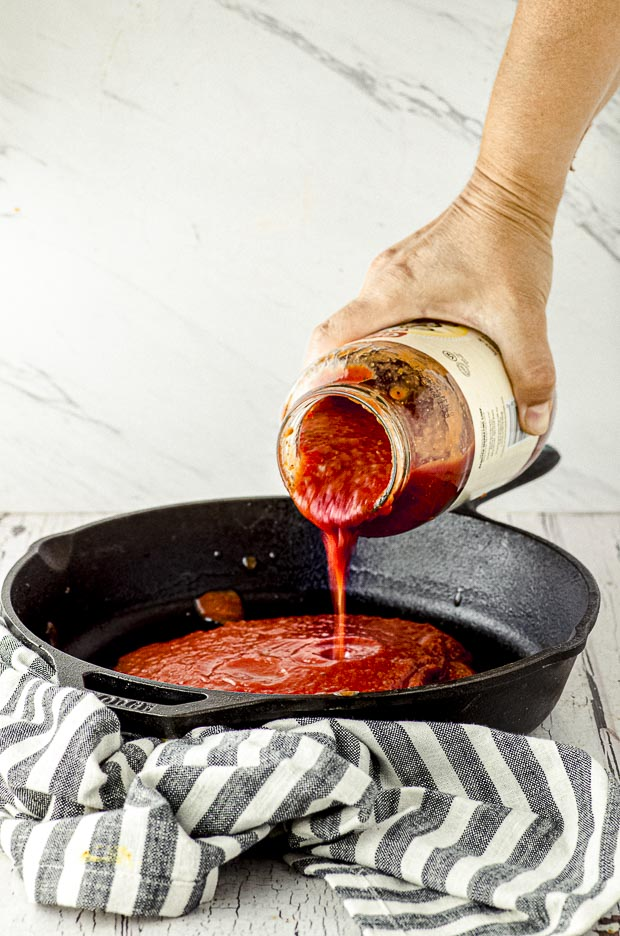 pouring sauce on a cast iron pan