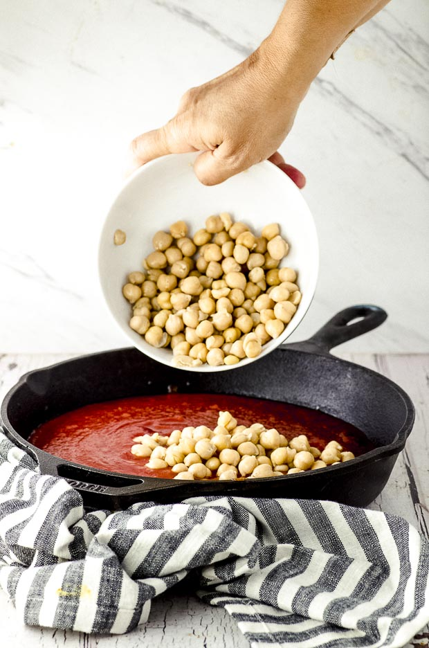 Adding chickpeas to tomato sauce in a cast iron pan