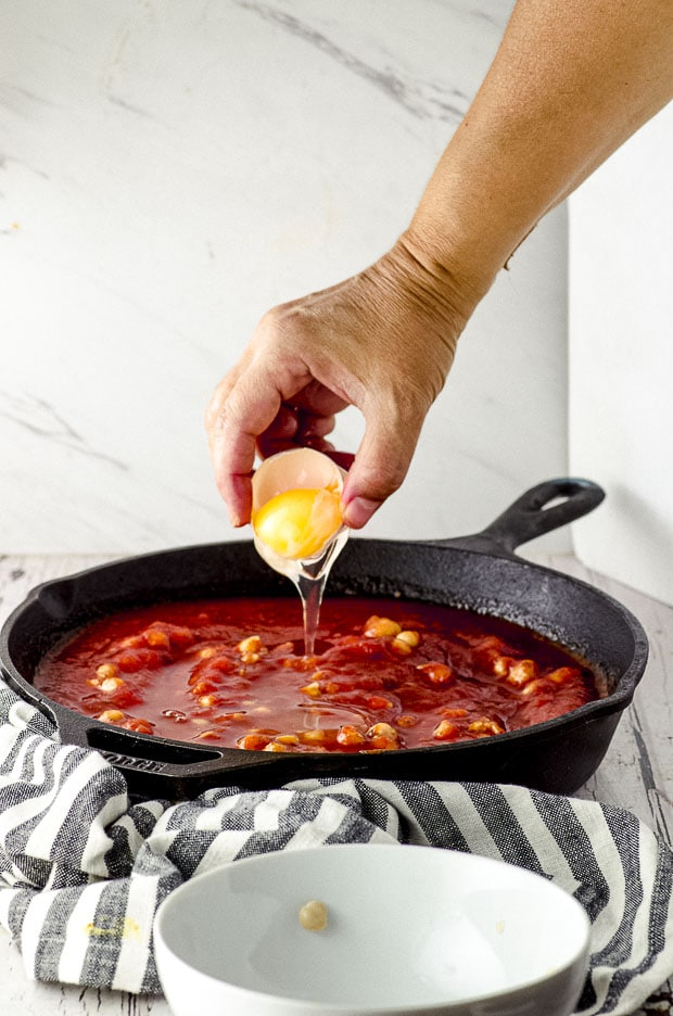 Adding eggs to tomato sauce in a cast iron pan