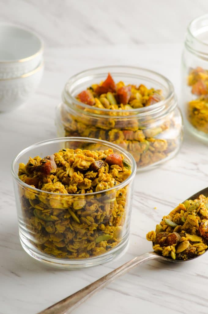 Several different sized jars with tahini granola with apricots and pistachios