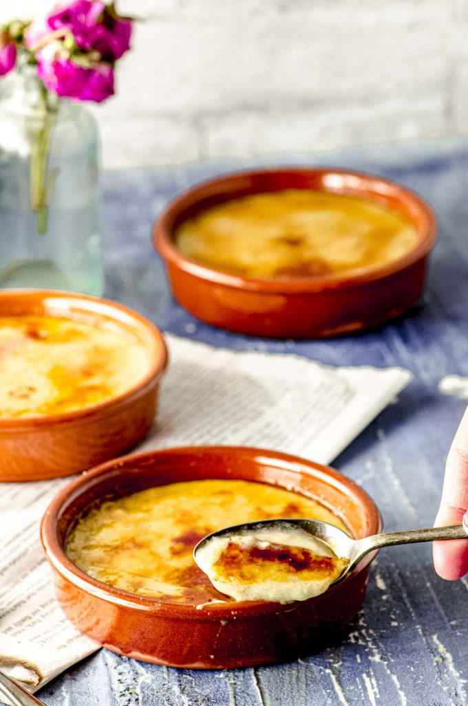 Scooping out some Crema Catalana out of a terracotta ramekin