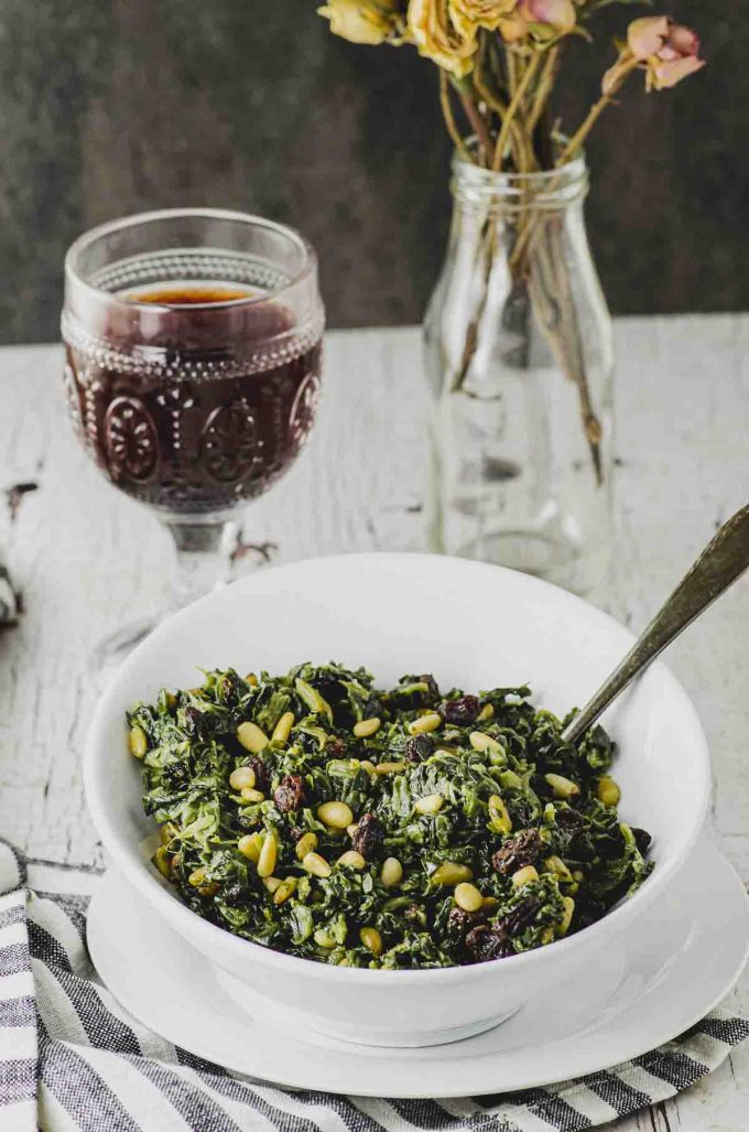 Side view of a white bowl filled with spinach with pine nuts and a raisins with a glass of red wine in the background.
