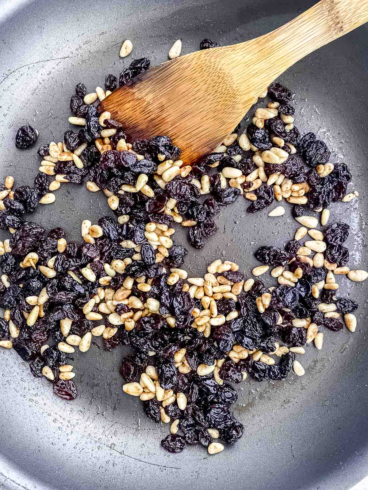 Sauteing pine nuts and raisins in olive oil in a nonstick pan