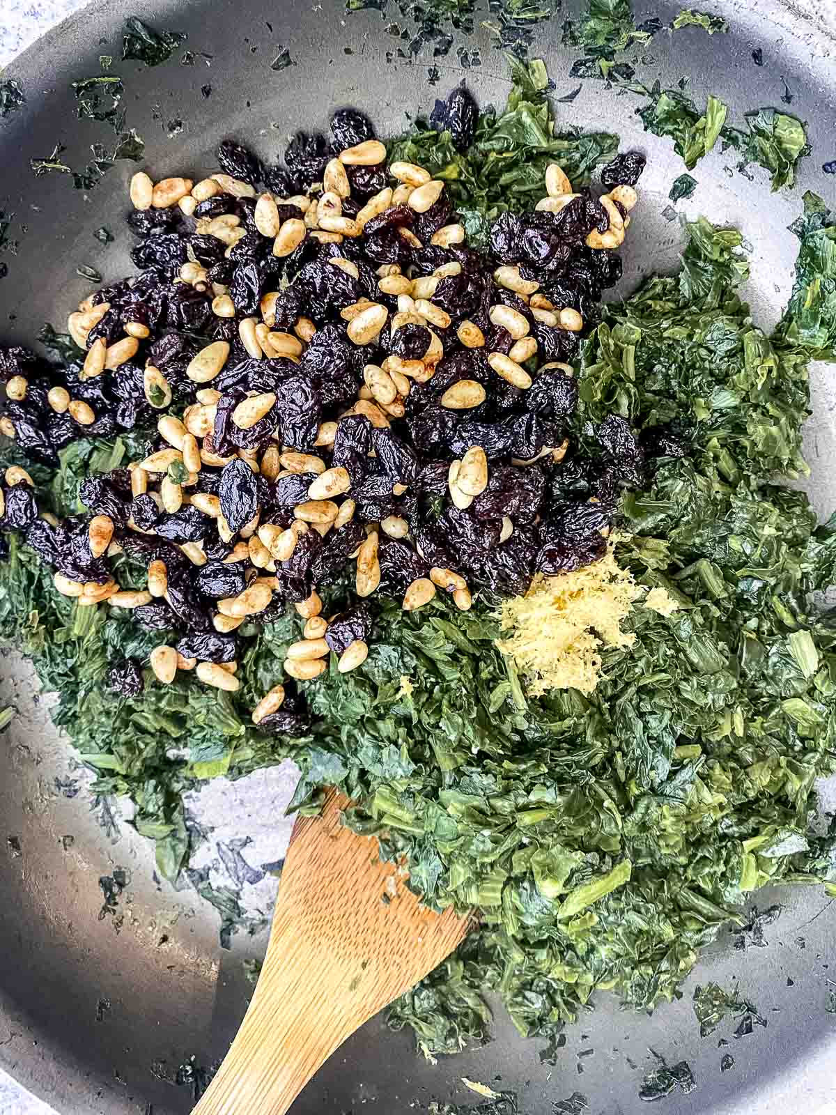 cooked spinach, pine nuts, raisins and lemon zest in a nonstick skillet
