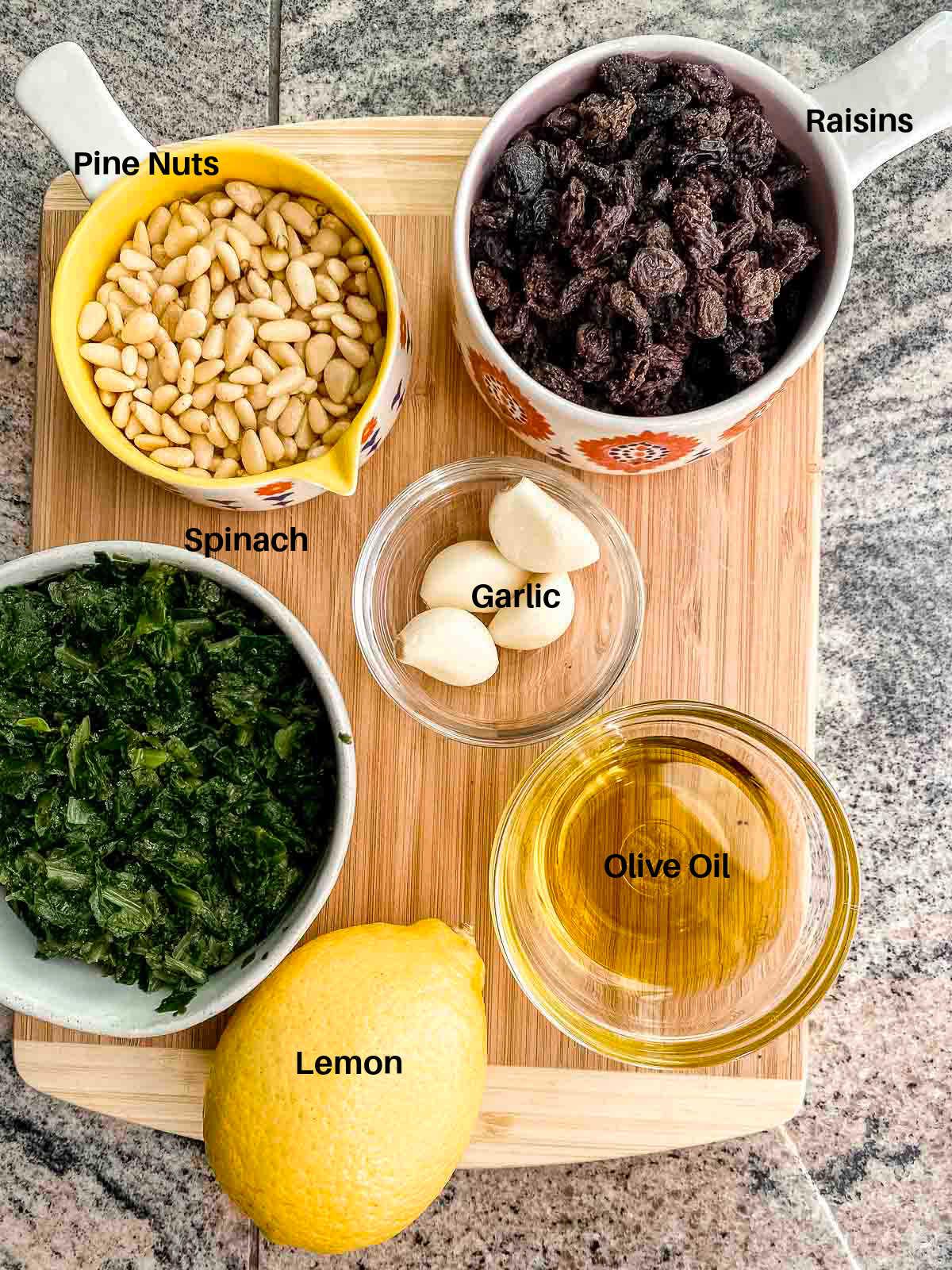 Ingredients to make espinacas a la catalana: spinach, raisins, olive oil, garlic, raisins, pine nuts and lemon