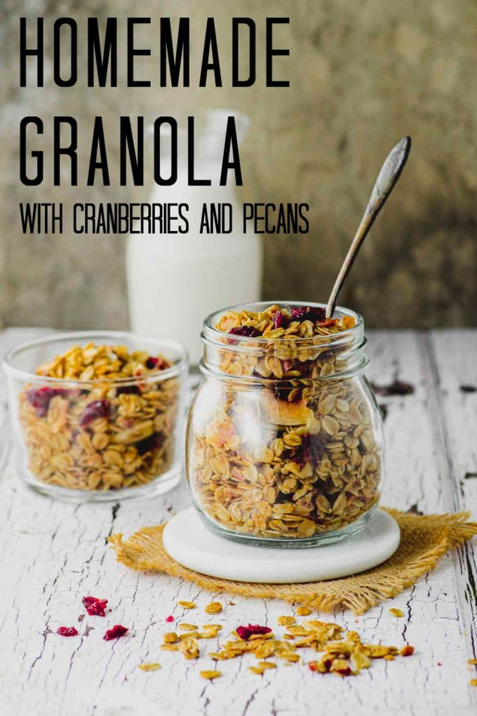 A jar filled with homemade granola with a spoon sticking out of the jar and a small bottle of milk in the background