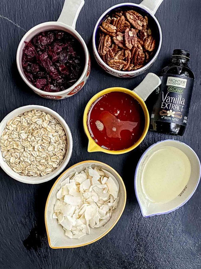 ingredients for homemade granola. Oats, oil, maple syrup, coconut flakes, vanilla extracts, raw pecans, dried cranberries