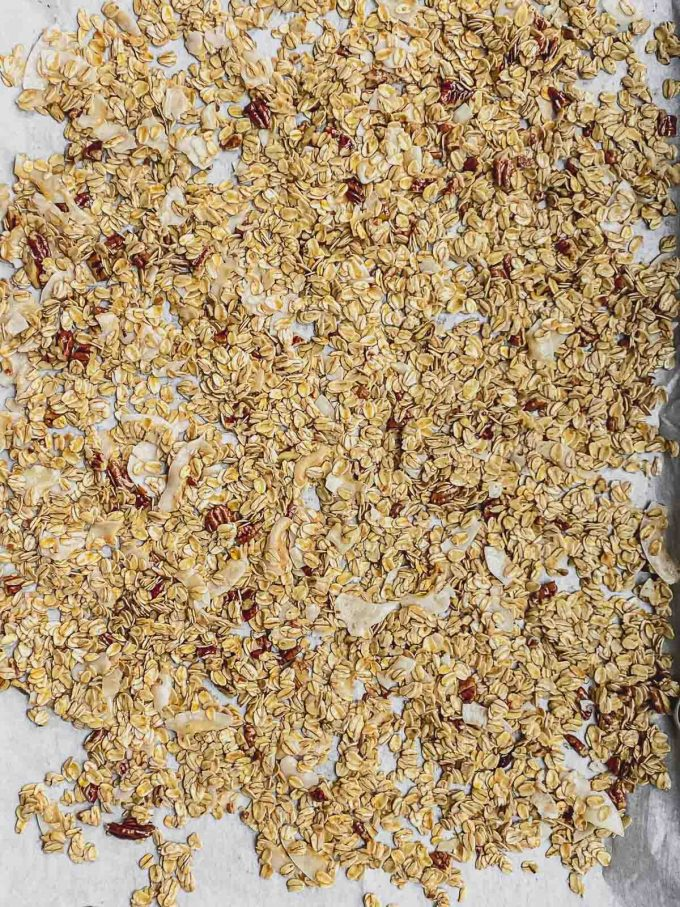 Spreading granola on a baking sheet ready to bake in the oven
