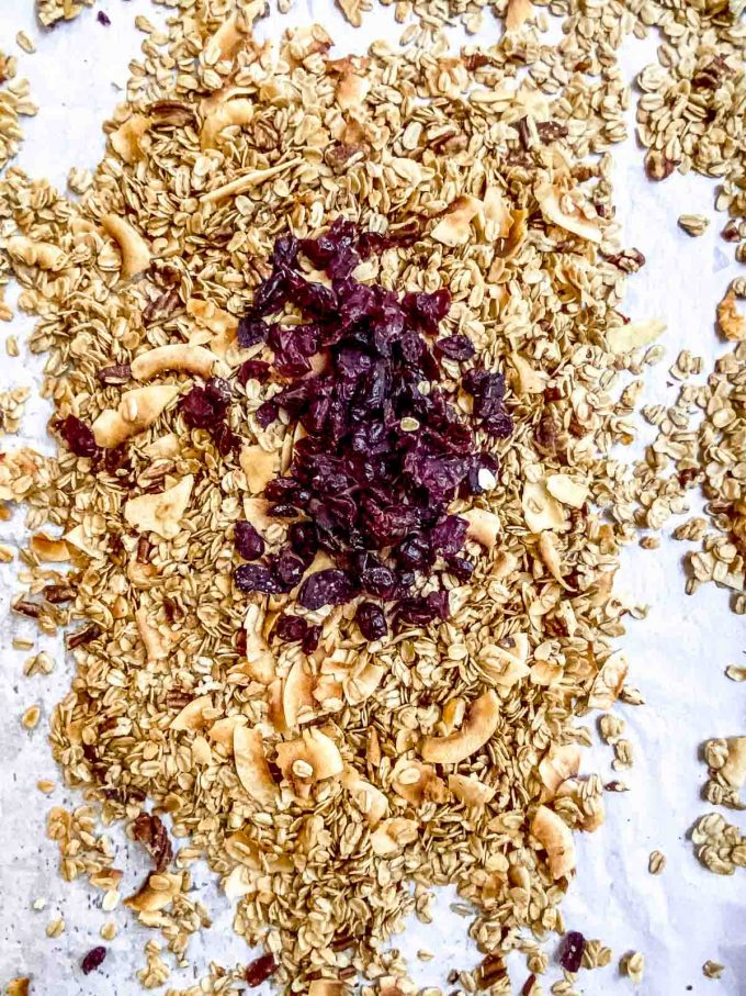 Adding dried cranberries to cooked granola