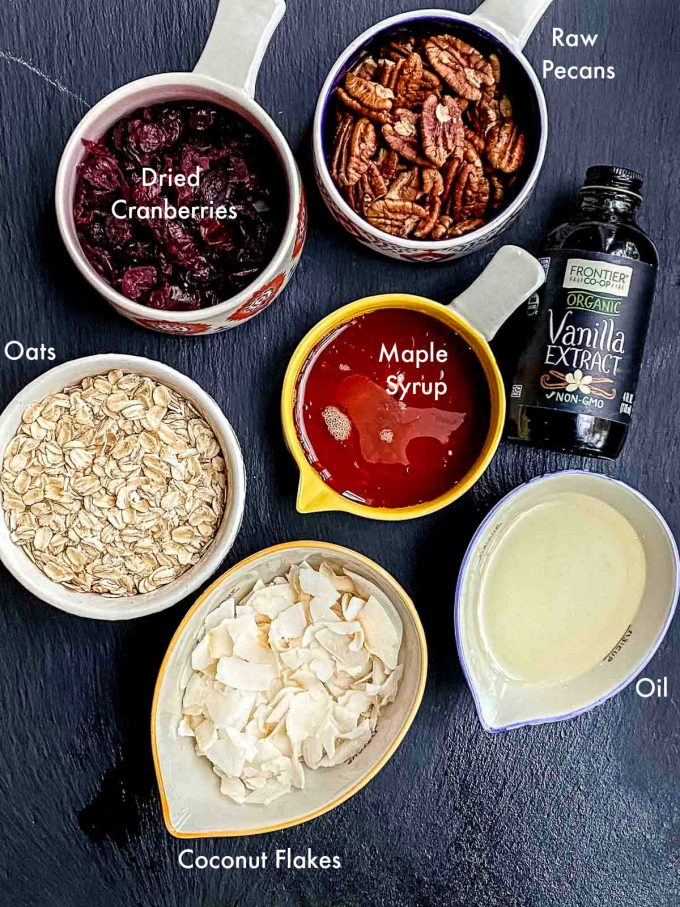 Labeled ingredients for homemade granola. Oats, oil, maple syrup, coconut flakes, vanilla extracts, raw pecans, dried cranberries