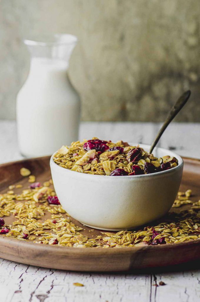 A white bowl filled with granola and placed on a larger round wood plate