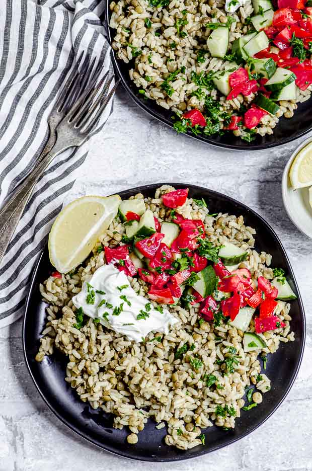 Close uo overhead view of a plate of mujadara ( rice and lentil ) topped with plain yogurt tomatoes and cucumbers