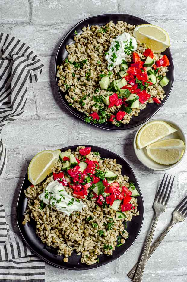 Bird's eye view of two black plates filled with mujadara ( rice and lentils dish) and topped with plain yogurt, cucumbers and tomatoes
