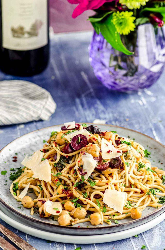 Side view of a plate with chickpea pasta with a purple vase with flowers in the background