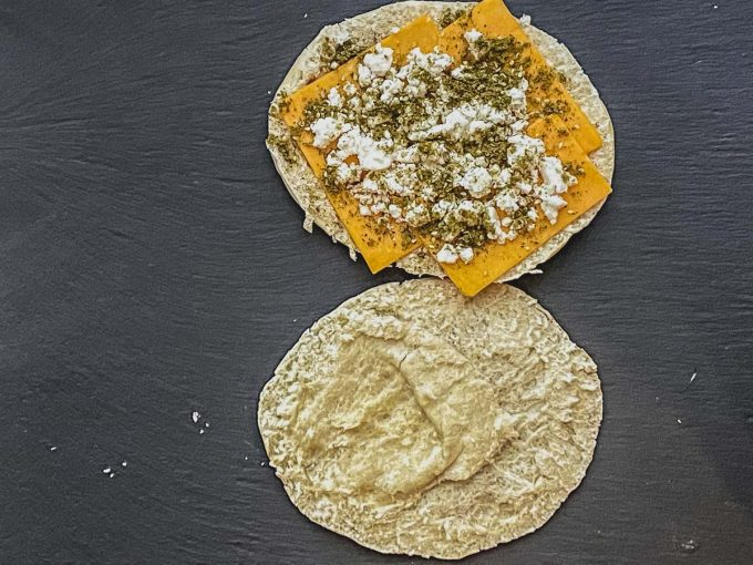 a pita bread split in half. On one half there is cheddar cheese, feta cheese and zaatar