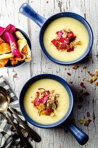 bird's eye view of two bowls of celeriac soup topped with vegetable chips
