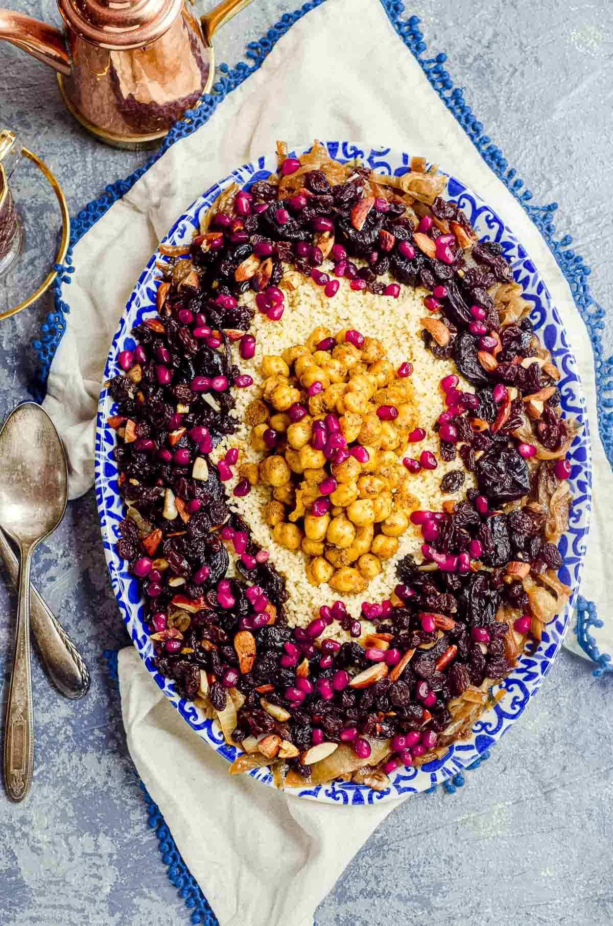 overhead view of an oval serving dish with moroccan couscous with prunes, raisins, almonds and pomegranate seeds