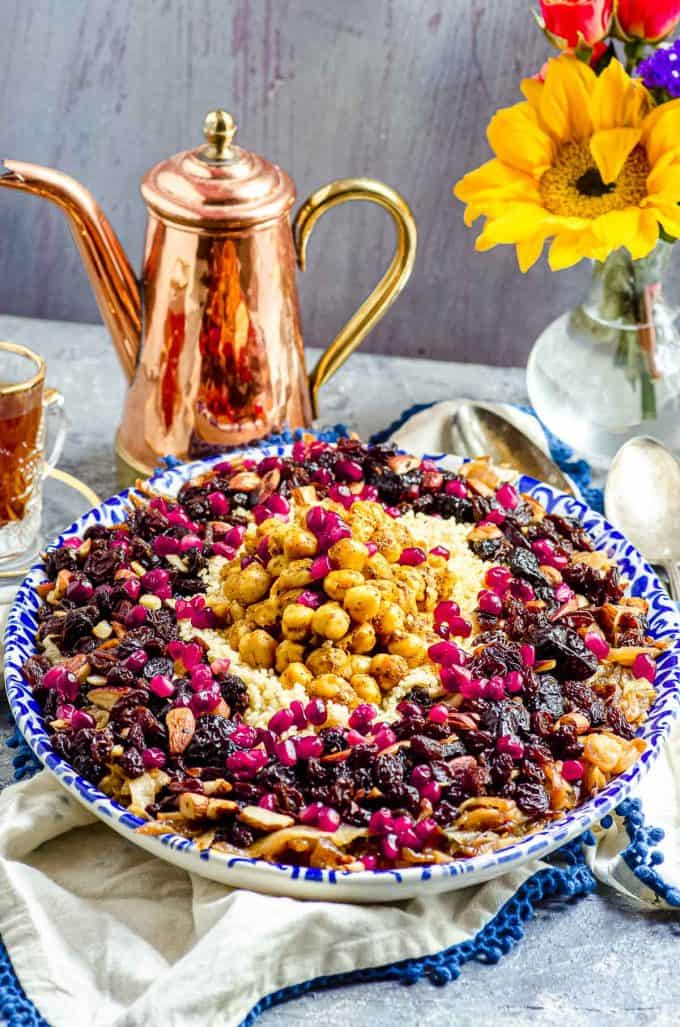 Side view of an oval serving dish with moroccan couscous topped with spices chickpeas and pomegranate seeds