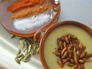 A terra cotta bowl filled with creamy celeriac soup topped with spiced pumpkin seeds and a plate filled with spices