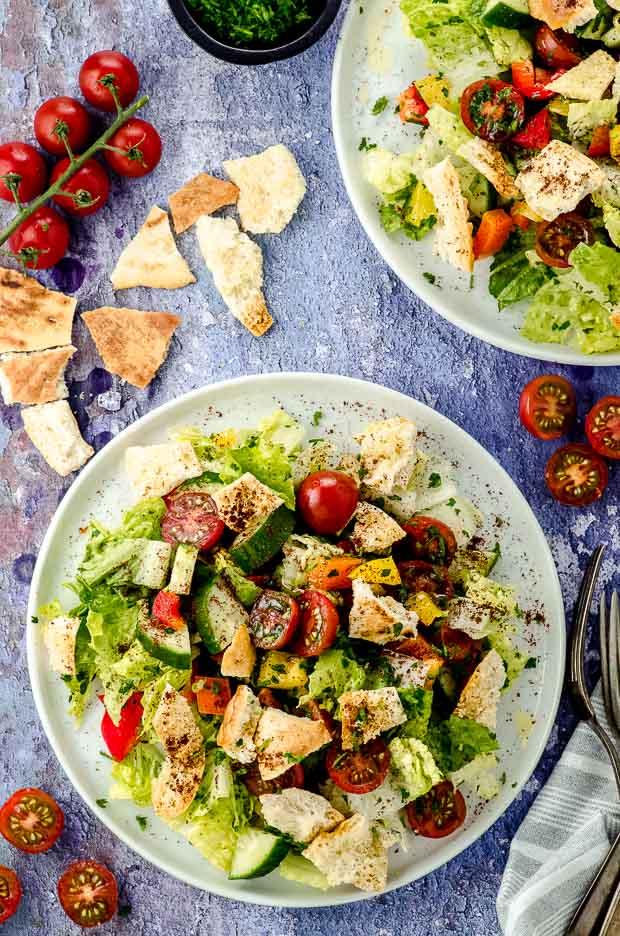 Bird's eye view of two white plates with Fattoush salad