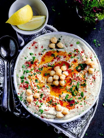 Overhead view of a plate with hummus garnished with some chickpeas, olive oil, paprika and chopped parsley