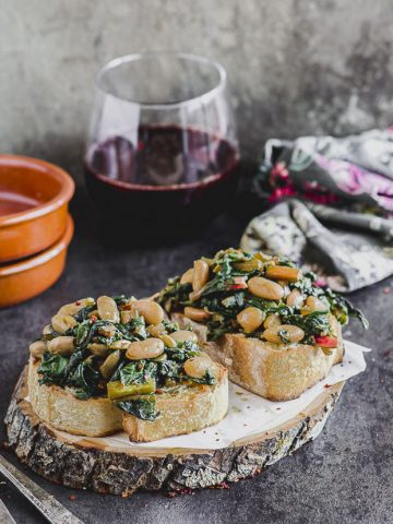 Side view of two slices of sourdough bread with sautéed chard with cannellini beans