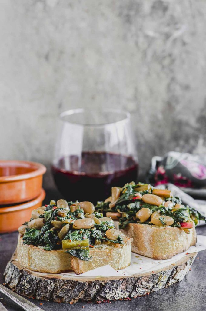 two slices of country bread with sautéed swiss chard and cannellini beans