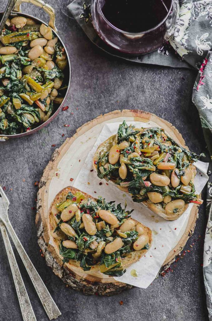 overhead view of two slices of sourdough bread with Swiss chard and cannellini beans next to a serving dish with sauté Swiss chard