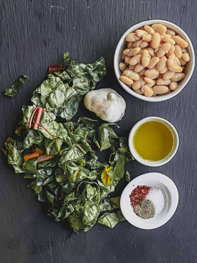 Ingredients to make Swiss chard with white beans: Rainbow chard, garlic, olive oil, canned cannellini bean, salt, pepper and red pepper flakes