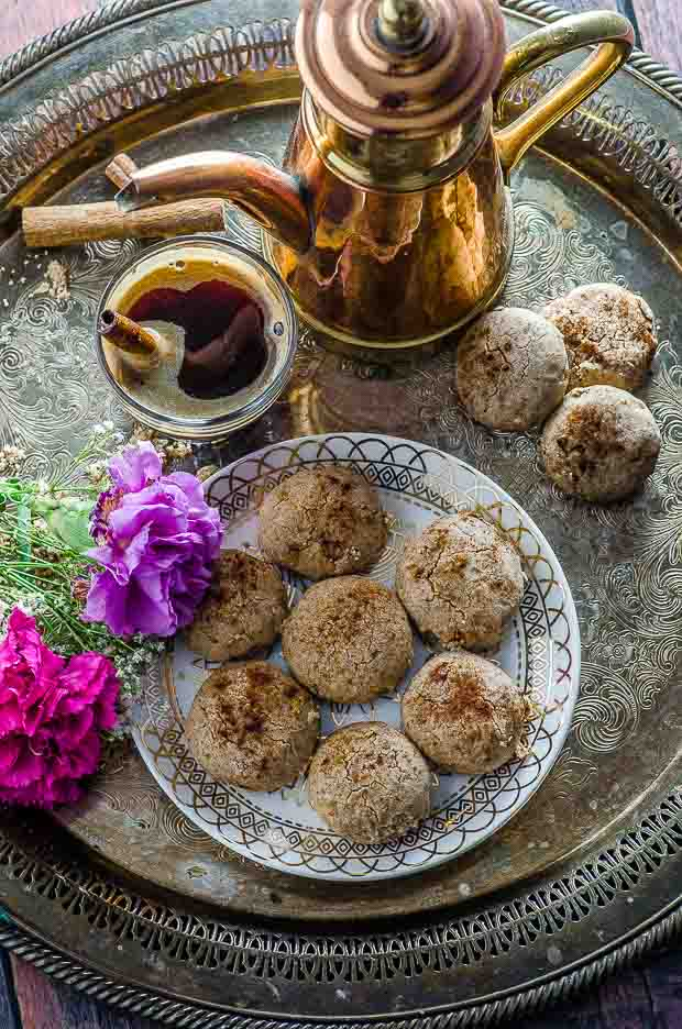 Bird's eye view of an old metal tray with a plate of Moroccan cinnamon cookies, a cup of coffee and a Moroccan style coffee pot