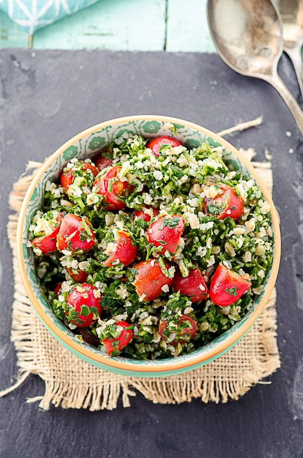 close up birds's eye view of A red and white bowl filled with tabbouleh salad