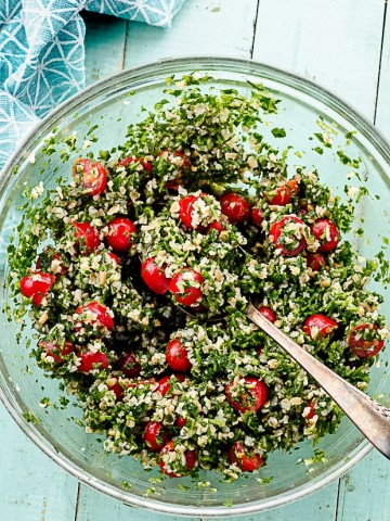 A clear serving bowl filled with tabbouleh salad
