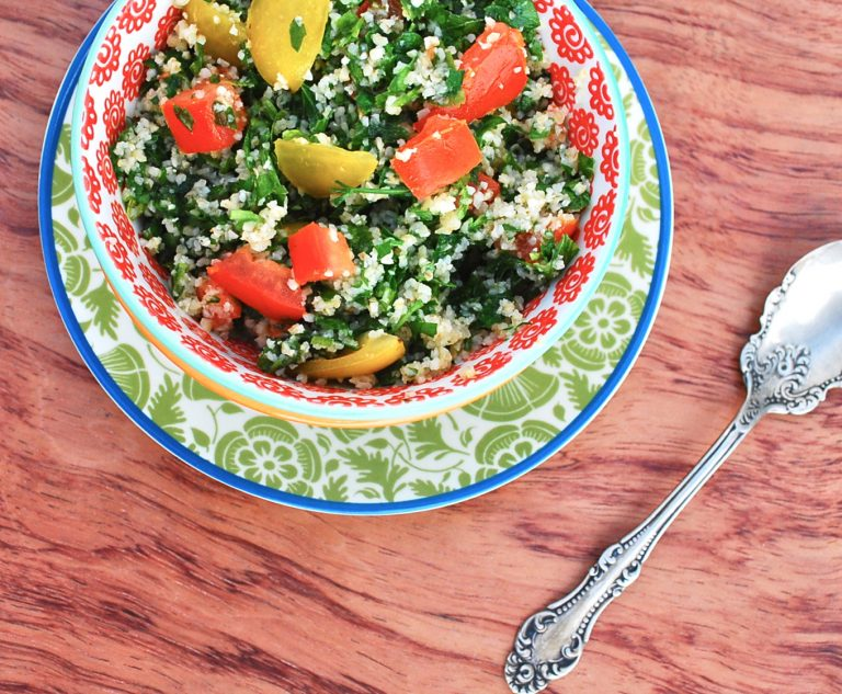Bird'e eye view of a Tabouleh salad placed inside a white and orange printed bowl. Under the bowl there is a white and green printed plate with a blue rim. There is a spoon on then right hand side. Everything is on a brown Woden surface.