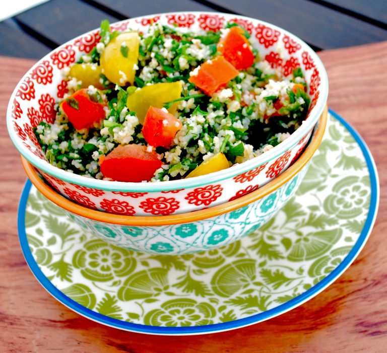 Tabouleh salad placed inside a white and orange printed bowl. The Bowl is placed on top of a white and green bowl and everything is under a white and green printed plate with a blue rim. Everything is on a brown Woden surface.
