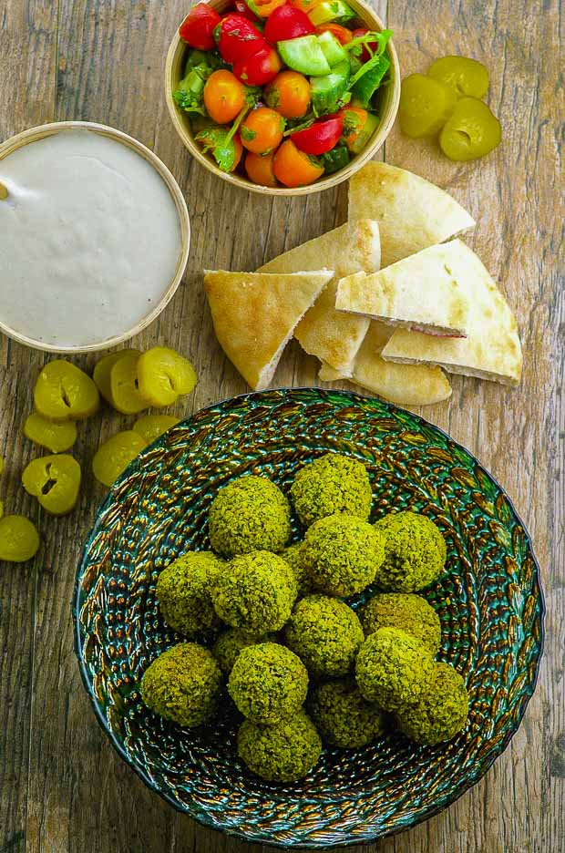 A green plate with Baked falafel, a bowl of tahini, a bowl or tomato cucumber salad and some pita bread and sliced pickles spread on the tabletop surface