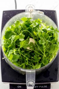 Fresh parsley and cilantro in a food processor bowl