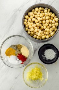 Bird's eye view of 4 bowls with chickpeas, spices, baking powder and lemon zest