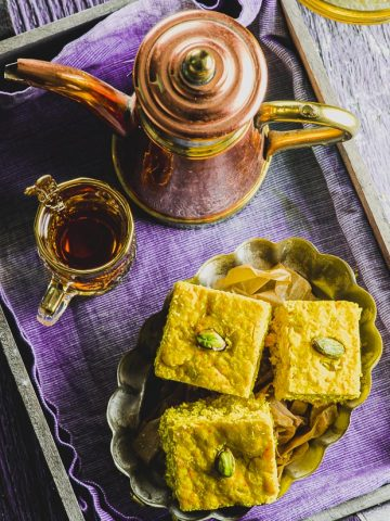 Overhead view of a tray lined with a purple napkin and a plate with three pieces of turmeric cake next to a copper tea pot and a small clear glass with tea