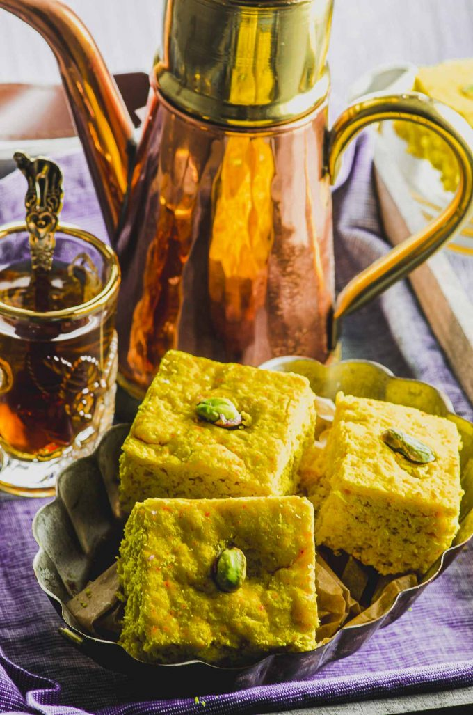 Side view of a plate with 3 pieces or turmeric cake next to a copper tea pot and a clear glass withtea