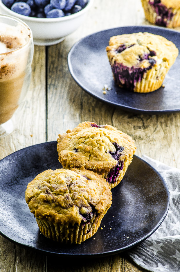 Two Vegan Coconut Blueberry Muffins on a black plate, another Vegan coconut Blueberry Muffin on a mother back plate in the background. both plates are on a Woden surface and there is also a small white bowl with fresh blueberries