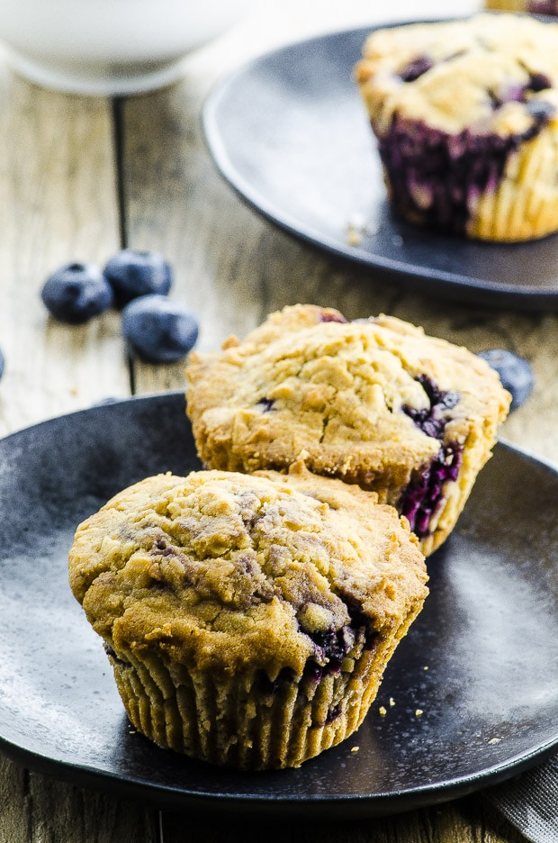 Two Vegan Coconut Blueberry Muffins on a black plate, another Vegan coconut Blueberry Muffin on a mother back plate in the background. both plates are on a Woden surface and some fresh blueberries are scattered on it.