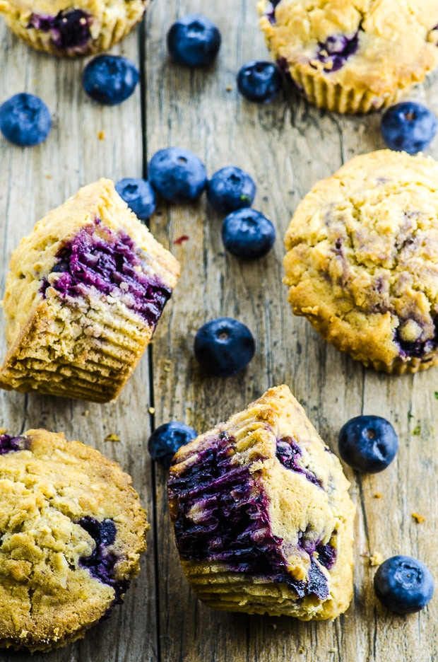 5 blueberry coconut muffins scattered on a wooden surface