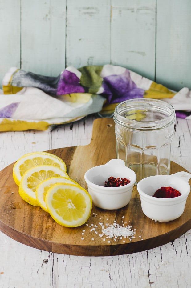 Lemons, paprika and empty jars to make preserved lemons