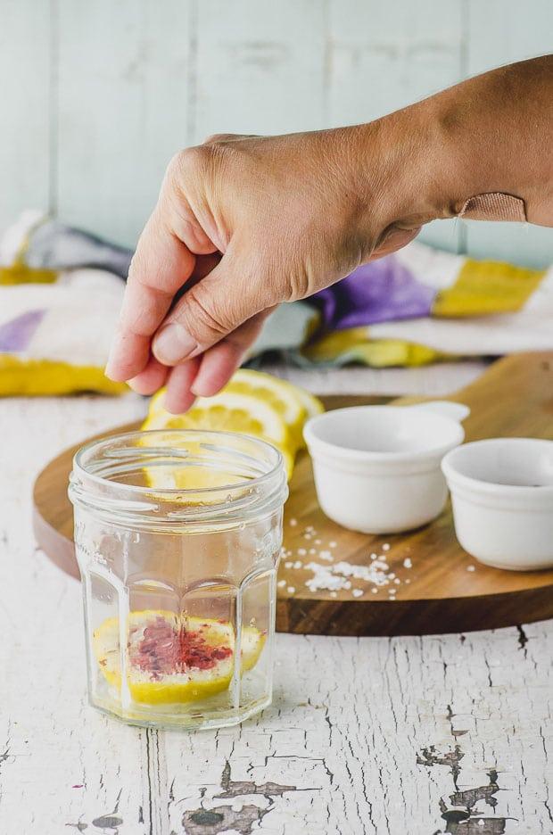 Sprinkling salt and paprika on a jar of preserved lemons