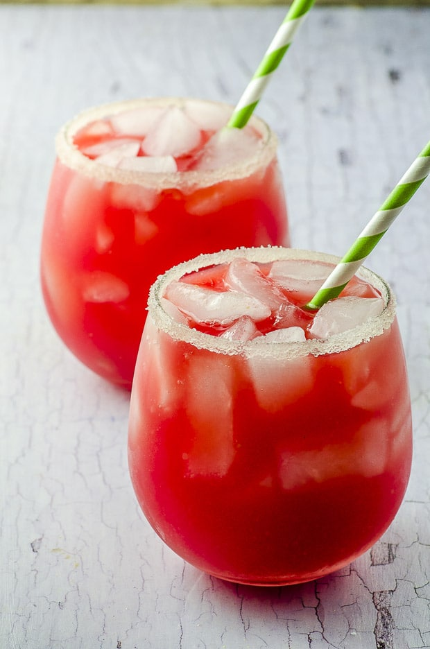 two glasses filled with watermelon lemonade and ice with a green and white paper straw