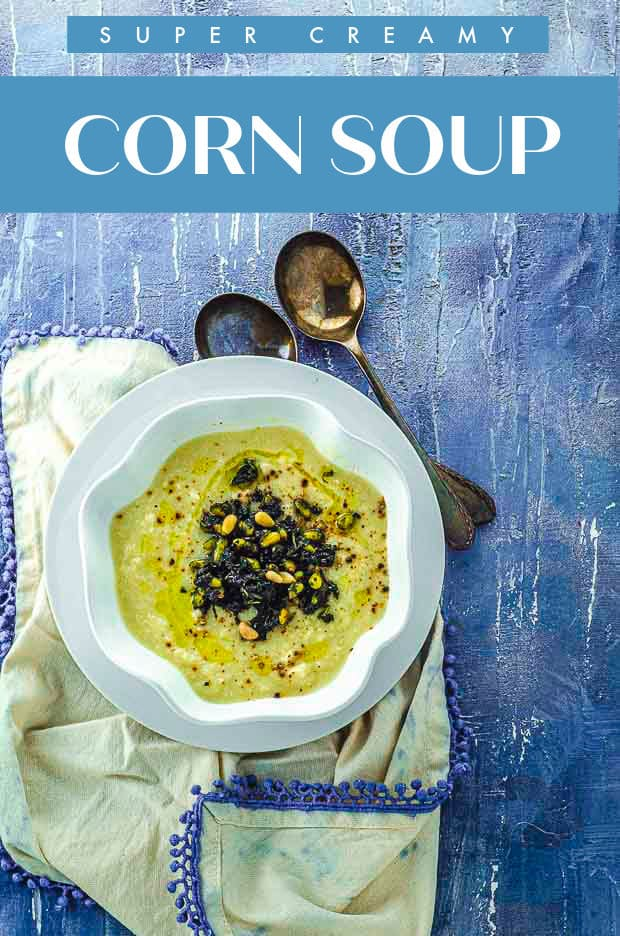 Overhead view of a bowl of creamy corn soup on a blue surface. there is a title that reads super creamy corn soup.