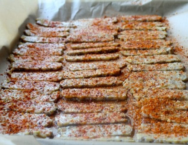 Tempeh with spices sprinkled on it on a baking sheet lined with parchment