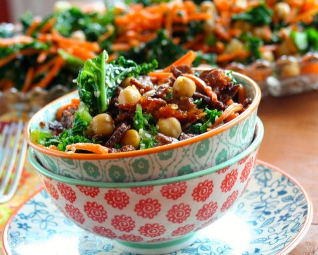 Two stacked bowl filled with kale salad with spicy tempeh bits