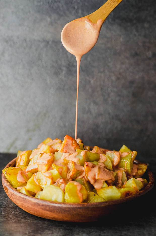 pouring bravas sauce on to a plate of potatoes to make patatas bravas a traditional tapa from Spain. One of our vegetarian Passover recipes.