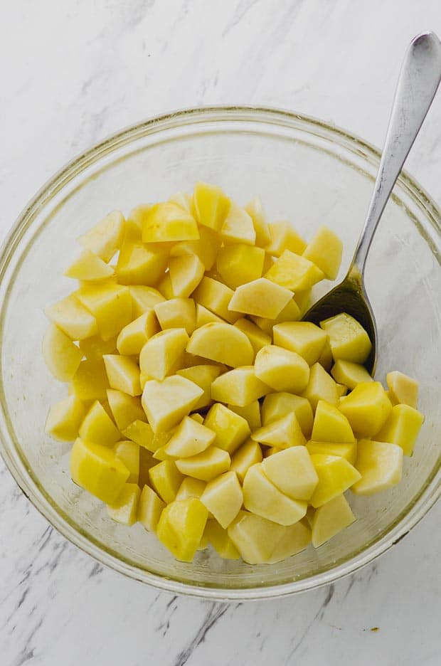 Mixing raw chopped potatoes with olive oil and salt in a a glass bowl.